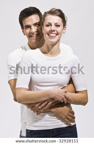 An attractive young couple posing.  They are wearing white. The male has his arms wrapped around the female.  They are smiling happily at the camera. Vertically framed photo. - stock photo