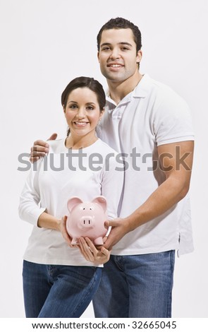 An attractive young couple posing together and holding a piggy bank.  They are smiling directly at the camera.  Vertically framed shot. - stock photo