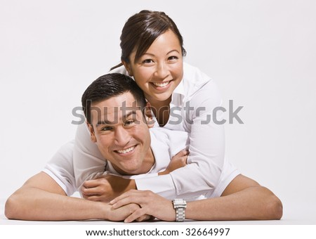 An attractive young couple posing together on the floor.  They are smiling directly at the camera.  Horizontally framed shot. - stock photo