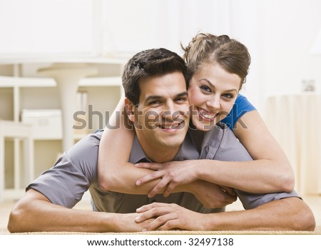 An attractive young couple posing together. The female is on his back and has her arms around his neck affectionately. They are smiling at the camera. Horizontally framed shot. - stock photo