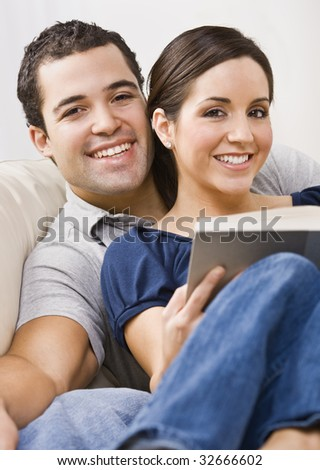 An attractive young couple relaxing together.  The female is holding a book and they are smiling directly at the camera. Vertically framed photo. - stock photo