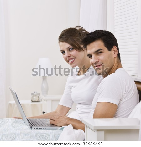 An attractive young couple sitting in bed together and holding a laptop.  They are smiling into the camera and are both wearing white. Square framed photo. - stock photo