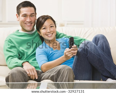 An attractive young couple sitting on a couch and watching television.  They are smiling directly at the camera.  The female is holding a remote.  Horizontally framed photo. - stock photo