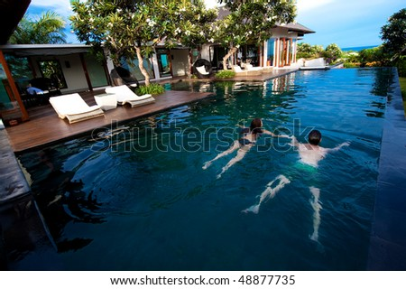 An attractive young couple swimming in a pool outdoors - stock photo