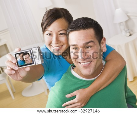 An attractive young couple taking their own picture with a digital camera. They are smiling.  The female is holding the camera. Horizontally framed shot. - stock photo