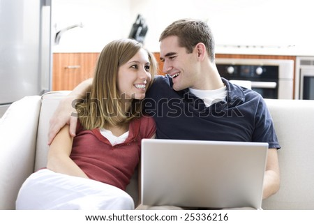 An attractive young couple uses a laptop together at home. - stock photo