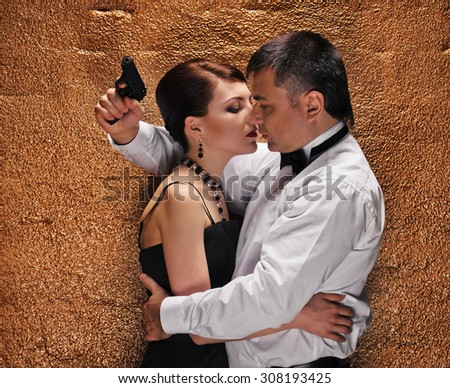 An attractive young couple with gun about wall - stock photo