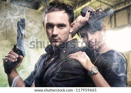 An attractive young couple with guns - stock photo