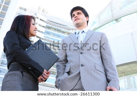 An attractive young diverse business man and woman team in office environment