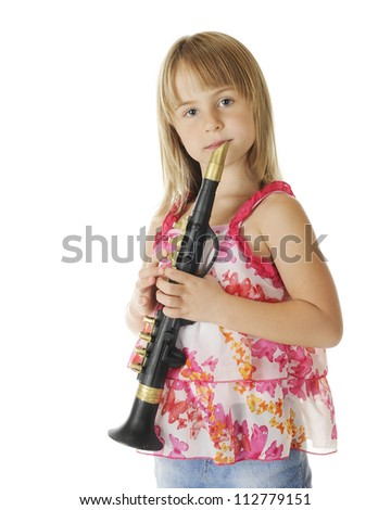 An attractive young elementary girl holding her clarinet, ready to play.  On a white background. - stock photo