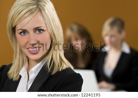 An attractive young female executive in focus in the foreground while her colleagues work on a laptop behind her