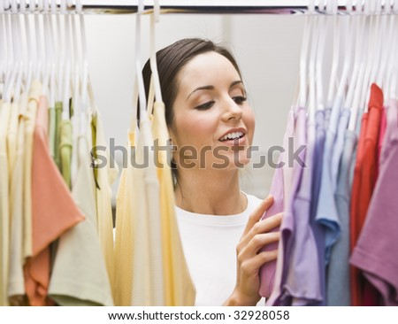 An attractive young female looking through a clothing closet.  She is smiling.  Horizontally framed photo. - stock photo