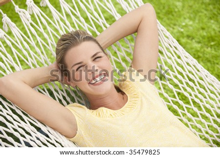 An attractive young female relaxing outside in a hammock.  She is smiling.  Horizontally framed shot.
