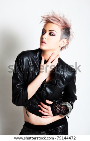 An attractive young female wearing punk fashion looks to the side with a blank expression. Vertical shot. - stock photo