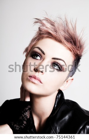 An attractive young female with a serious expression is wearing a punk hairstyle with pink hair. Vertical shot. - stock photo
