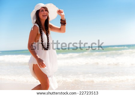 An attractive young girl posing with a cool hat on the beach - stock photo