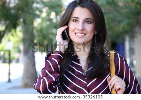 An attractive, young indian business woman on phone