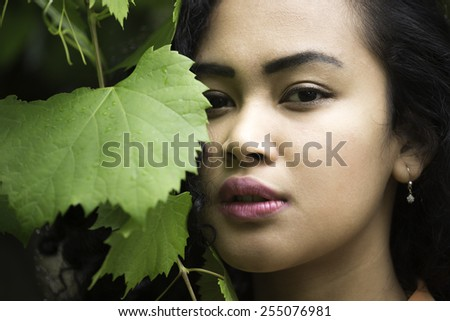 An attractive young Indonesian woman next to a grape vine. - stock photo