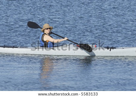 An attractive young lady is paddling along in tropical waters of Mission Bay, San Diego, California.
