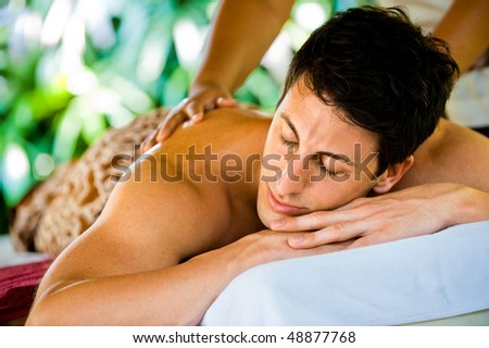 An attractive young man enjoying a back massage at a spa outdoors - stock photo