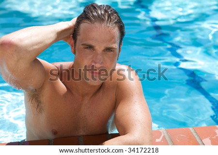 An Attractive Young man in the pool blue background - stock photo