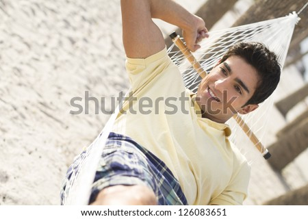 An attractive young man lying in a hammock on the beach.