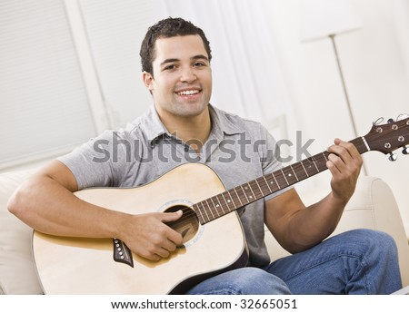 An attractive young man playing the guitar.  He is seated on a couch and is smiling at the camera.  Horizontally framed shot.