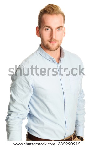 An attractive young man wearing a blue shirt with khaki pants, standing smiling towards camera against a white background. - stock photo
