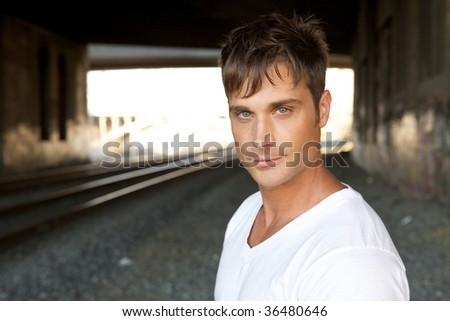 An Attractive Young Man with a Smirk at the Camera - stock photo