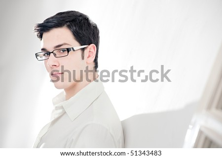 An attractive young man with glasses on white background looking at the camera