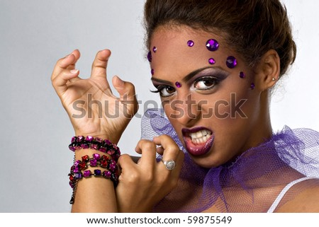 An attractive young model with glamorous makeup and gemstones in a fierce pose. - stock photo