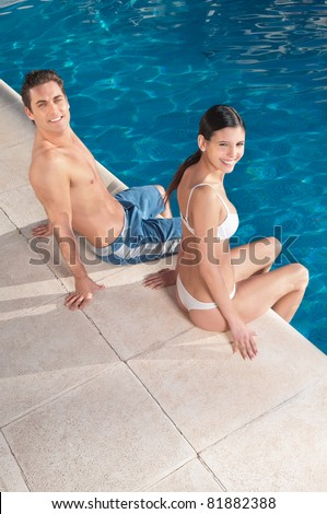 An attractive young smiling couple relaxing by the pool - stock photo