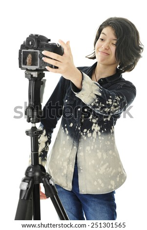 An attractive young teen critiquing adjustments on her pro camera, hoping to get a great selfie.  Her image is visible on the camera's viewing screen.  On a white background. - stock photo