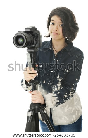 An attractive young teen looking at the viewer as she holds onto the tripod that supports her pro camera.  On a white background. - stock photo