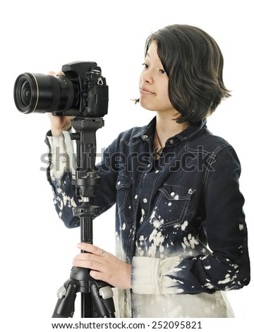 An attractive young teen patiently waiting for the right moment before clicking her tripod held camera for a great shot.   On a white background. - stock photo