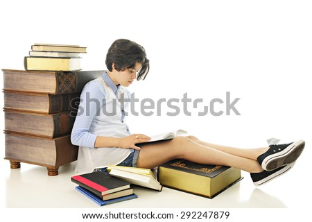 An attractive young teen reading one of the books that surround her.  On a white background. - stock photo
