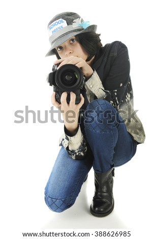 An attractive young teen school photographer squatting to shoot from a low position.  On a white background. - stock photo