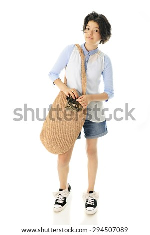 An attractive young teen taking a walk with her pet cat polking his head out of her tan shoulder bag.  Focus is on the girl.  On a white background. - stock photo