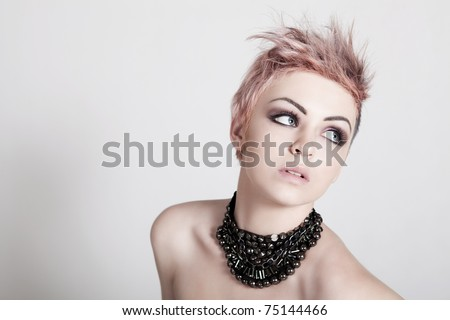 An attractive young topless female with a serious expression is wearing a necklace and looking down. Horizontal shot. - stock photo