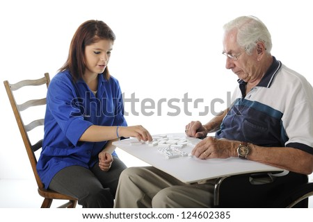 An attractive young volunteer playing Dominoes with an elderly man in a wheelchair.  On a white background. - stock photo