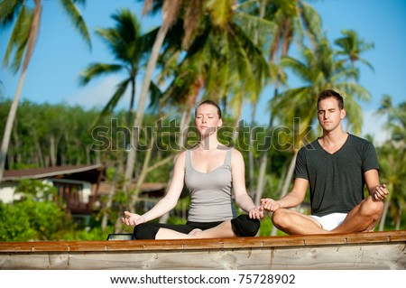 An attractive young woman and man doing yoga on a jetty with a tropical island villa behind - stock photo