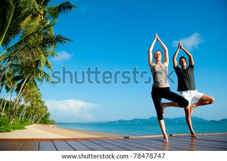 An attractive young woman and man doing yoga on a jetty with the blue ocean and another island behind them - stock photo
