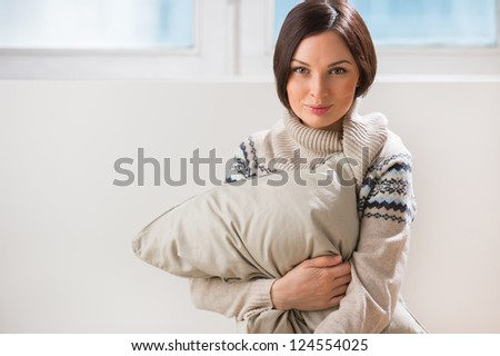 An attractive young woman daydreaming and misses her couple, embracing pillow at living room - stock photo