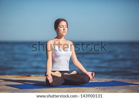 An attractive young woman doing yoga on a jetty with the blue ocean. Series - stock photo