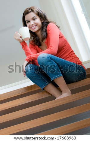An attractive young woman drinking on the stairs