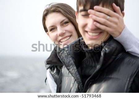 An attractive young woman embracing her handsome boyfriend - stock photo