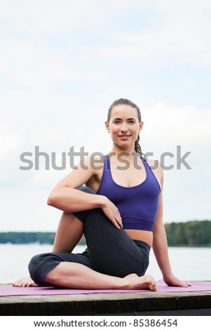 an attractive young woman excercises yoga outdoors - stock photo