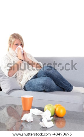 An attractive young woman feeling very bad while sitting at home on her couch.