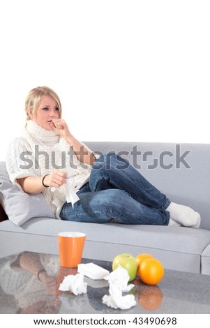 An attractive young woman feeling very bad while sitting at home on her couch. - stock photo