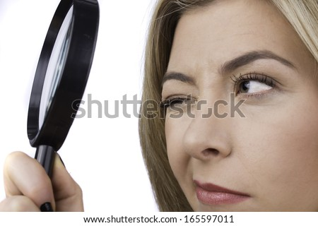 An attractive young woman gazes through a large magnifying glass. - stock photo